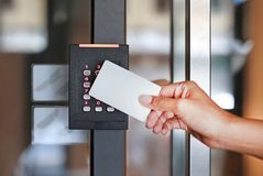 Door access control. Young woman holding a key card to lock and unlock door Stock Photos