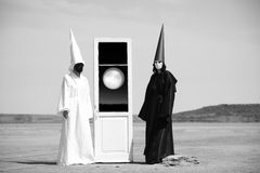 Door into another world. Two strange people in black cloak and white cloak and the door into another world Royalty Free Stock Images