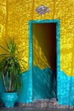 Door in arabic style. Doors painted bright yellow and turquoise color and mottled shadows. The decoration in the shape of a fish above the door is a symbol of Royalty Free Stock Images