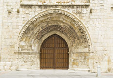 Door with arcades. Front view of a religious edifice entrance with wooden door and stone arcades Stock Photography
