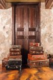The door and the bag. Vintage used travel suitcases. Many old vintage suitcase. Luggage concept.  Stock Photo
