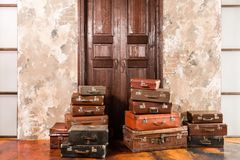 The door and the bag. Vintage used travel suitcases. Many old vintage suitcase. Luggage concept.  Stock Photos