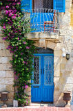 The door and balcony entwined with bougainvillea on Birgu. Malta. The view of beautiful Maltese style door and balcony entwined with bougainvillea on Birgu Stock Images