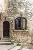 Door with barred window. In an old wall france. It´s a vertical picture Royalty Free Stock Photo