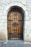 Door behind  lattice in stone wall Royalty Free Stock Image