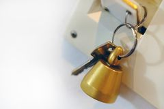 Door bell and keys, welcome home. Good quality photo of a key with some massive bronze bell. You may see two types of keys at the picture: classic metal key and Royalty Free Stock Photo