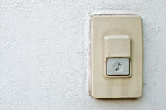 Door bell ring. Electronic door bell ring with music note sign on white wall Royalty Free Stock Photos