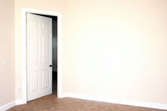 Door in big wall. A white door is slightly open leading the viwers eye to the room that is mostly hidden beside a big blank wall Stock Photos