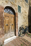 Door and Bike. Old wooden door and aged black bycicle. Tuscany Classic Royalty Free Stock Image