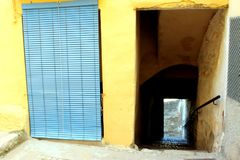 Door with blue sunblind and narrow street with stairs that go down. In Bocairent village, Valencia, Spain stock images
