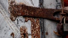 Door bolted with a padlock. The door lock is rusty and bolted with a big padlock stock video