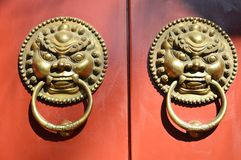 Door buckle of red wood door. Near the Confucian Temple in Beijing, the red doors of every household have such a door fastener with lions.This symbolizes stock photo
