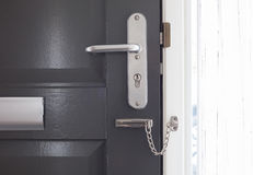 Door chain on a grey door. Security measures royalty free stock photography