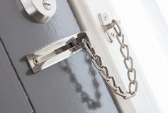 Door chain on a grey door. Security measures stock images