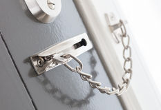 Door chain on a grey door. Security measures stock photo