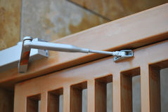 Door Closer. A photo taken on a door closer installed on a wooden door Stock Photos