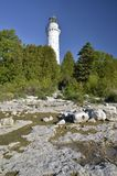 Door County Wisconsin's Guardian. Cana Island lighthouse located in famous Door County Wisconsin, surrounded by lush trees and receeding water front of Lake stock image
