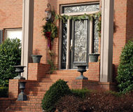 Door Decorated for Christmas. The entrance way of a brick luxury home with planters, wreaths and garlands to celebrate the Christmas Holiday season Stock Photo