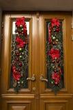 Door decorated of fir, flowers and balls. Christmas decor Stock Photos