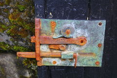 Door detail. Detail of old wooden door with colorful rusty bolt Royalty Free Stock Photography