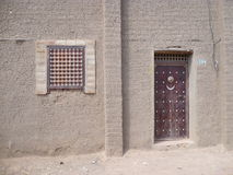 Door in Djenne, Mali. Along a quiet, dusty street in the world heritage town of Djenne, Mali, a door and a window merely hint at what might be behind Royalty Free Stock Images