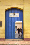 Door entrance of a school for kids in Trinidad, Cuba. A couple of young alumns in Eduardo Garcia school, Trinidad royalty free stock photo