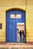 Door entrance of a school for kids in Trinidad, Cuba. A couple of young alumns in Eduardo Garcia school, Trinidad Royalty Free Stock Photo