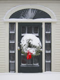Door entrance with wreath. Door entrance to home with holiday wreath and snow Royalty Free Stock Photography