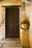 Door with flowers. Wooden door with vase of flowers Stock Image