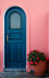 A door on a Greek island. Image shows a blue door with a flower pot decorating the entrance, captured on a Greek island royalty free stock photography