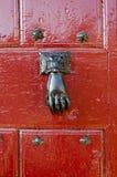 Door Hand Knocker. A decorative iron hand as a door knocker over a red door Royalty Free Stock Photography