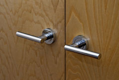 Door handle. Double door handle with wooden door texture in the background Royalty Free Stock Photos