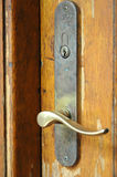 Door-handle. An old scratched wooden door with golden brass vintage door-handle without a key Royalty Free Stock Photos