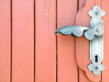 Door handle. Old red wooden door and metalic handle Royalty Free Stock Photography