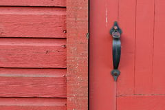 Door handle. Section of wall and door, including black metal handle of a historic red barn stock images
