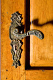 Door handle. Image of an old antique pewter door handle on a yellow wooden door Royalty Free Stock Images