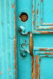 Door handle. Bright turquoise blue grunge door and worn brass door handle and key Stock Photography