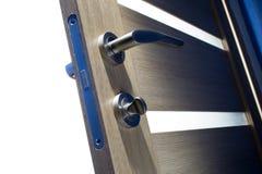 Door handle on the door is open. Ajar wooden door set into it by a magnetic lock chrome royalty free stock images