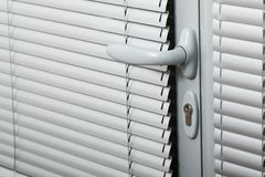 Door handle on a gray door with shutters Royalty Free Stock Photo