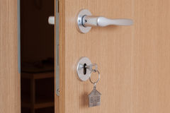 Door handle with inserted key with house icon keyring Stock Photo