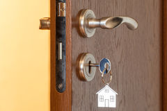 Door handle with inserted key in the keyhole and house icon on it Stock Image