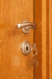 Door handle with inserted key in the keyhole and house icon on it Stock Photos