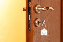 Door handle with inserted key in the keyhole and house icon on it Stock Photo