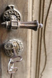 Door handle and key in old fortified church stock image