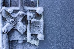 door handle and keyhole are covered with frost. severe frosts. door freezes. icy handle and lock covered with snowflakes. blurred stock image
