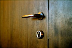 Door Handle and Lock. Brown wooden door with handle and lock stock image