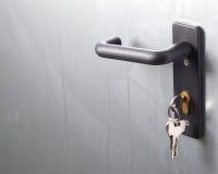 A door handle with lock and keys. The door is metallic stock image