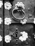 Door handle with lock, old door fragment, black and white image. A fragment of an old wrought iron door with a lock and ornaments in the form of sockets Stock Images