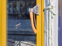 Door handle made of an ax. Creative design solution. Yellow door, the entrance to the cafe. Summer sunny day royalty free stock images