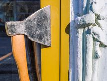 Door handle made of an ax. Creative design solution. Yellow door, the entrance to the cafe. Summer sunny day stock photo